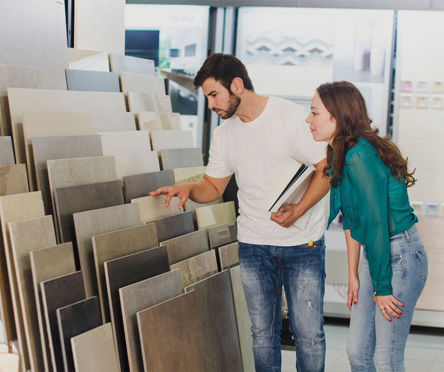 Couple in flooring store looking at samples of ceramic tile in different colors